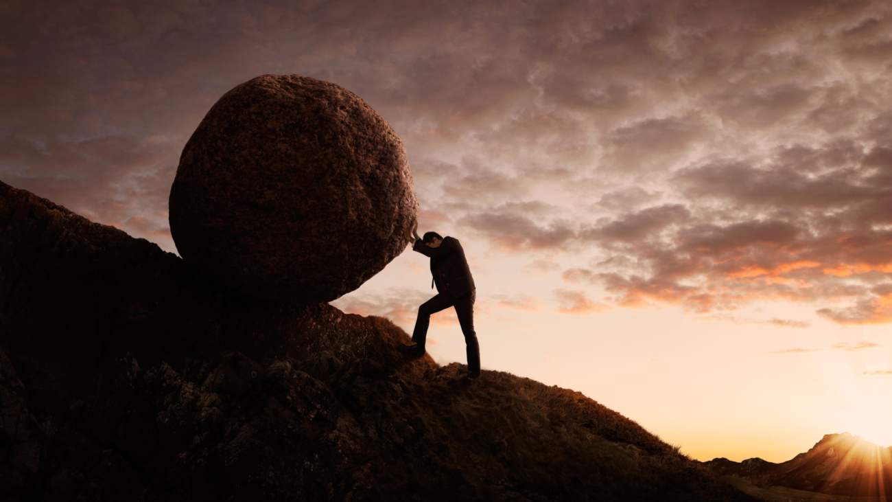 Business concept, Young businessman pushing large stone uphill with copy space